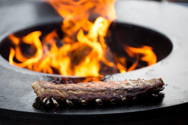 Costelinha de porco grelhada com molho barbecue na grelha. comida de rua do festival
