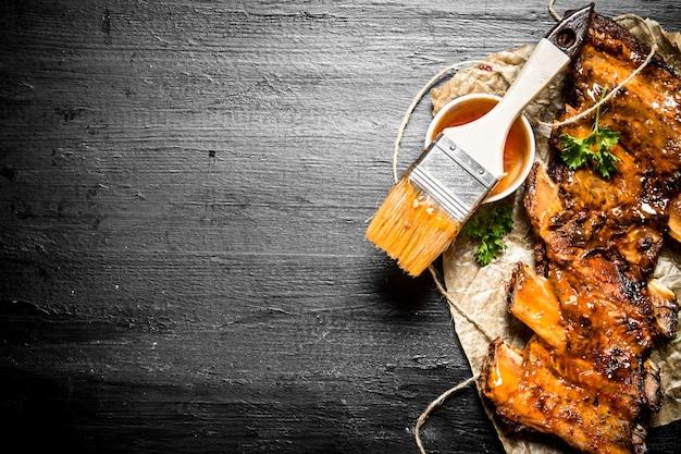 Costelinha de porco grelhada com molho picante e um pincel no quadro de giz preto
