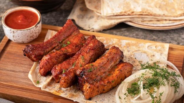 Costelinha de porco para churrasco com molho vermelho e cebola. carne grelhada