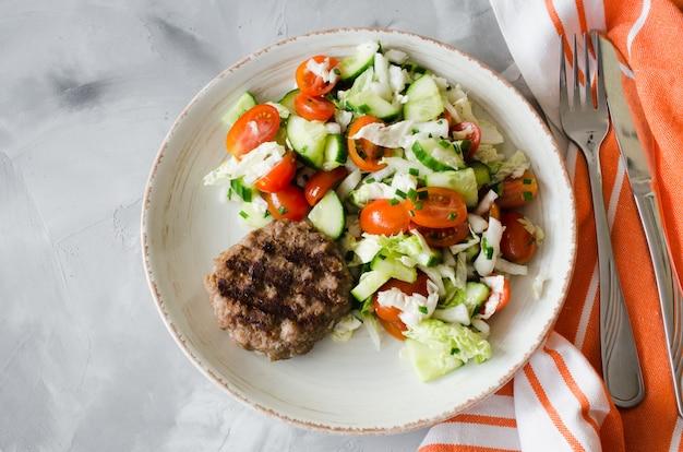 Costoleta grelhada suculenta com salada do legume fresco no fundo cinzento.