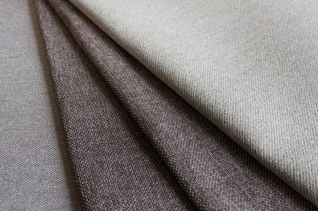 Costura à mão fazendo composição com camadas dobradas de tecido texturizado marrom escuro.