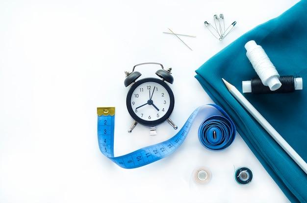Costura sob encomenda na hora. postura plana, cópia espaço. tecido azul, relógio, ferramentas de costura e acessórios de bordado: linhas, alfinetes, bobinas, botões, agulhas, fita métrica