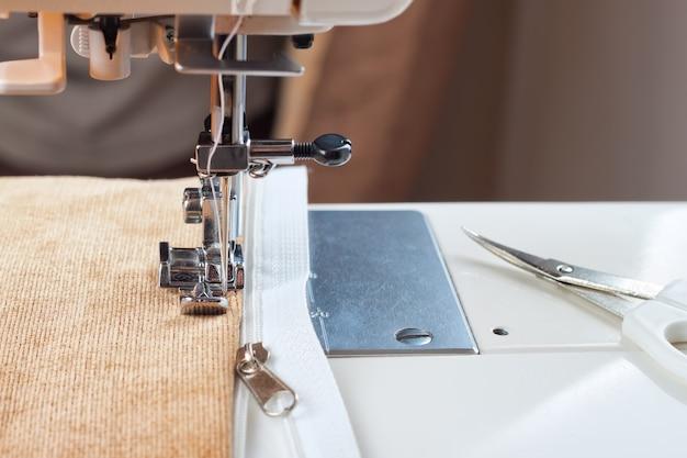 Costurando um zíper branco em uma máquina de costura. processo de costura