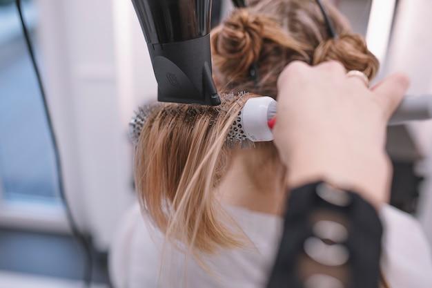 Costure estilista usando secador de cabelo e escova