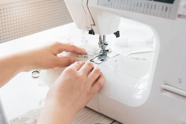 Costureira ajusta a máquina de costura para trabalhar