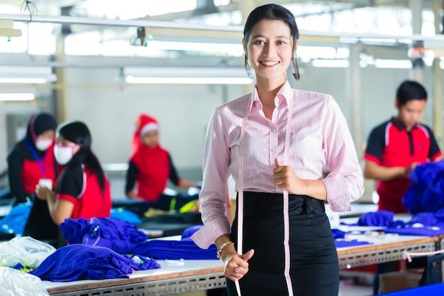 Costureira asiática em uma fábrica têxtil