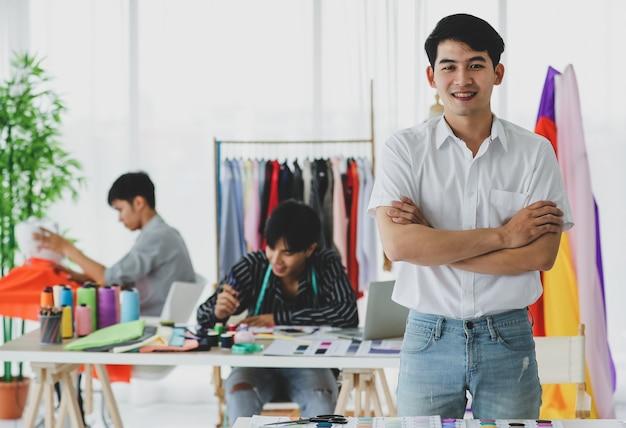 Costureira asiática positiva com os braços cruzados sorrindo ao olhar para a câmera enquanto está perto de colegas na oficina