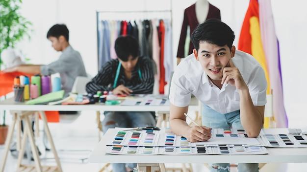 Costureira asiática positiva sorrindo ao olhar para a câmera enquanto está perto de colegas na oficina