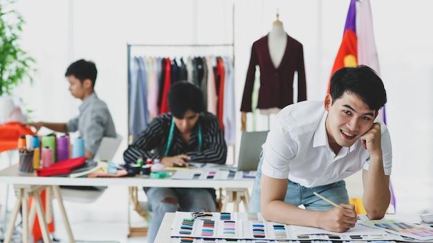 Costureira asiática positiva sorrindo e comparando amostra de cartela de cores enquanto está perto de colegas na oficina