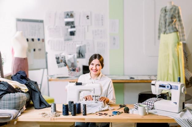 Costureira bonita que costura em sua oficina. costureira trabalhando na máquina de costura. alfaiate fazendo uma peça de vestuário em seu local de trabalho.