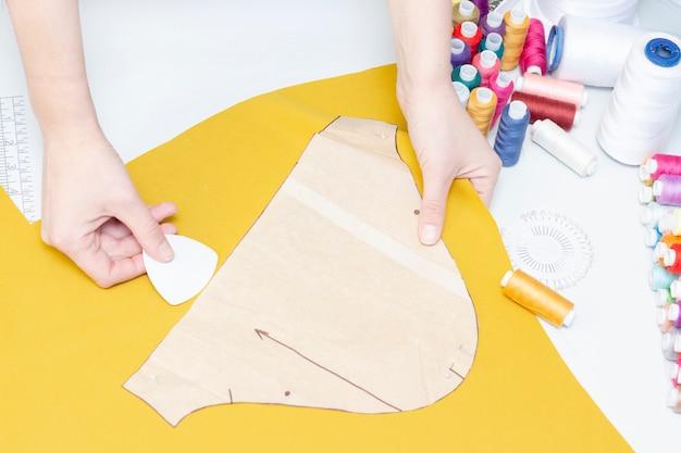 Costureira circunda o padrão no close-up do tecido. um conjunto de itens para bordar: linhas, agulhas, alfinetes, tesouras, fita métrica, etc.