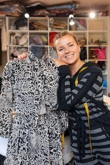 Costureira com manequim como estilista profissional. costureira feminina, ajustando as roupas na alfaiataria manequim e sorrindo