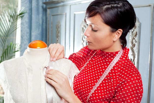Costureira com manequim trabalhando em casa