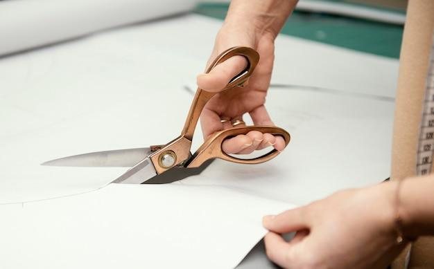 Costureira cortando tecido com tesoura