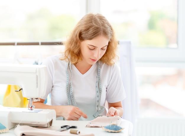 Costureira costura novo design pelas mãos
