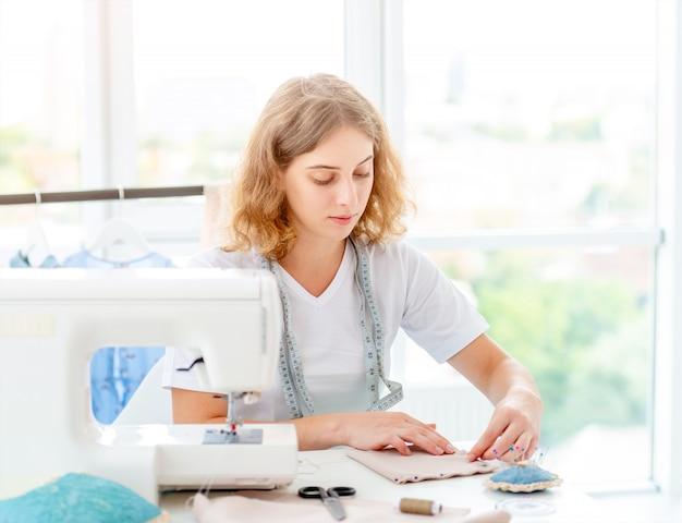 Costureira costura pelas mãos na oficina