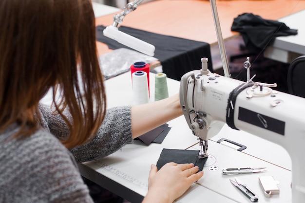 Costureira costurando na máquina