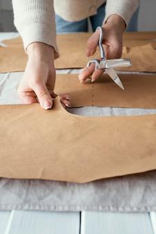 Costureira de alto ângulo usando uma tesoura para cortar o tecido