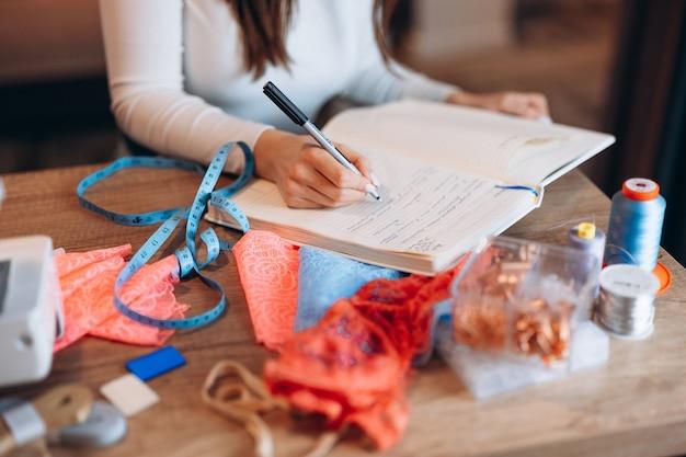 Costureira de close-up está escrevendo ideias na oficina. criação de cursos online de design de roupas.