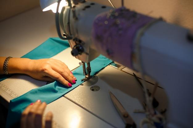Costureira de menina à luz de uma lâmpada de mesa costurando um pano azul em uma máquina de costura