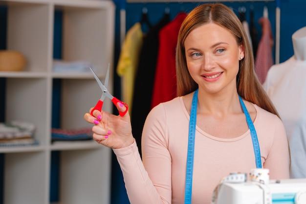 Costureira de mulher trabalhando na fábrica têxtil close-up