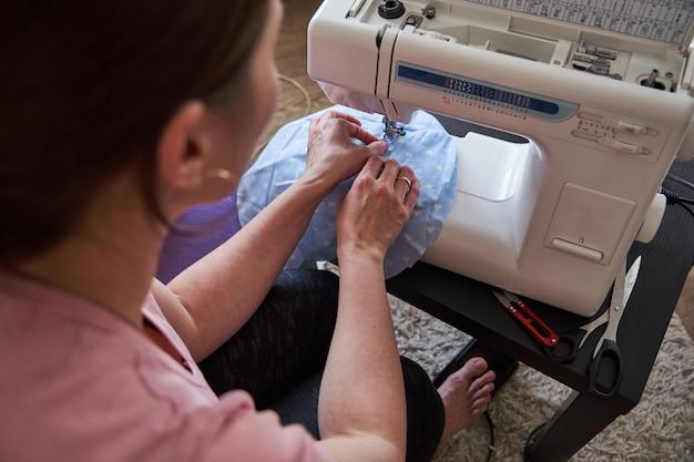 Costureira de omã que trabalha a máquina de costura. o processo de criação de brinquedos elefante com as mãos em casa. costurar como um hobby para a alma.