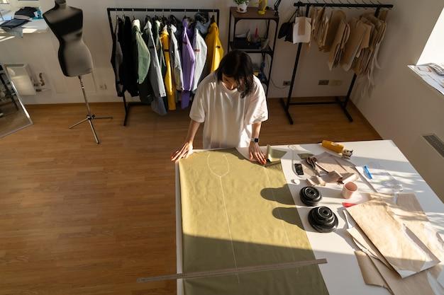 Costureira de processo de costura e corte trabalha com estampas em tecido para coleta no ateliê