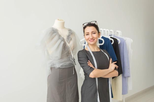 Costureira, designer de moda, alfaiate e conceito de pessoas - designer de moda linda mulher em pé no estúdio.