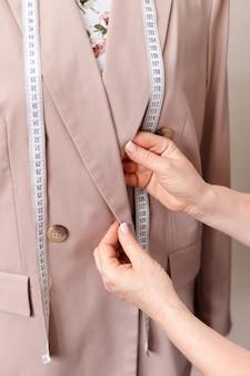 Costureira endireita gola em jaqueta bege
