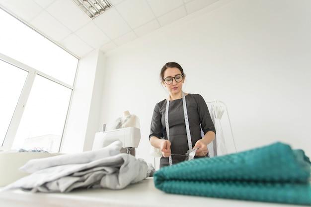 Costureira, estilista, alfaiate e conceito de pessoas - retrato de uma costureira trabalhando em seu próprio estúdio.