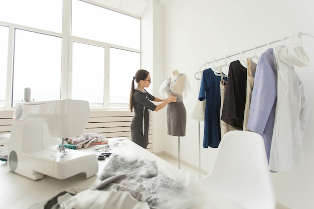 Costureira, estilista e conceito de alfaiate - a estilista decora a roupa no manequim