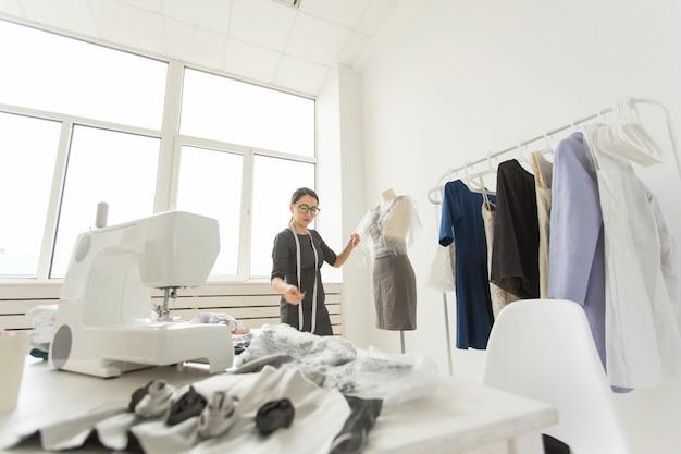 Costureira, estilista e conceito de alfaiate - a estilista decora o look no manequim.