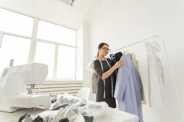 Costureira, estilista e conceito de alfaiate - a estilista escolhe os vestidos na prateleira.