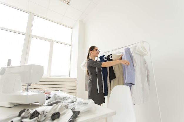 Costureira, estilista e conceito de alfaiate - a estilista escolhe os vestidos na prateleira