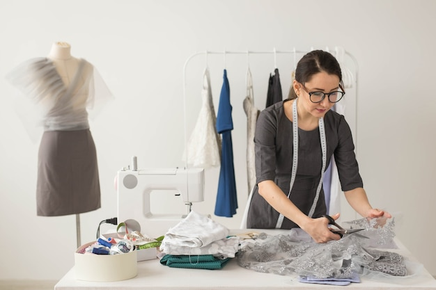 Costureira, estilista e conceito de alfaiate - jovem estilista corta tecidos leves
