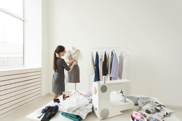 Costureira, estilista e conceito de alfaiate - jovem estilista talentoso escolhendo roupas para a nova coleção futura em seu próprio showroom.