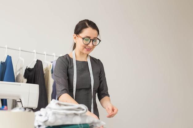 Costureira, estilista e conceito de alfaiate - mulher estilista trabalhando no estúdio.