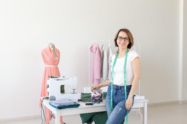 Costureira, estilista e conceito de alfaiate - mulher jovem costureira com uma costura na parede branca.