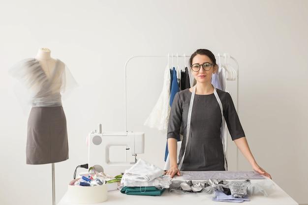 Costureira, estilista e conceito de alfaiate - mulher jovem costureira sobre cabideiro com fundo de vestidos.