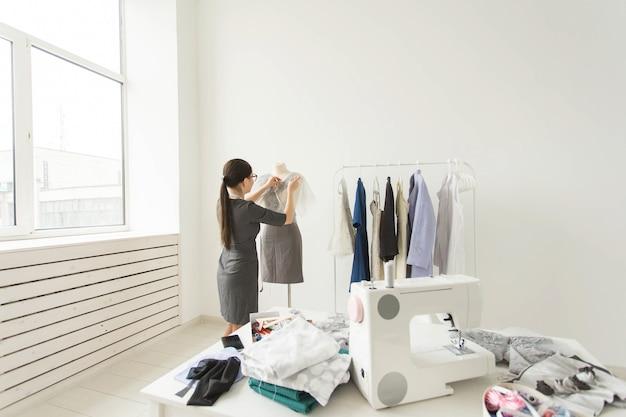 Costureira, estilista e conceito de alfaiate - processo de trabalho, estilista decora a roupa no manequim.