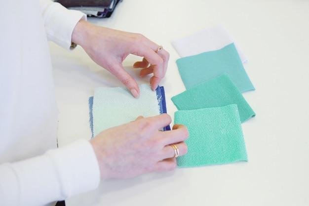 Costureira fêmea nova que escolhe o material do catálogo no estúdio. tailor procurando em tecidos em pé na oficina de costura