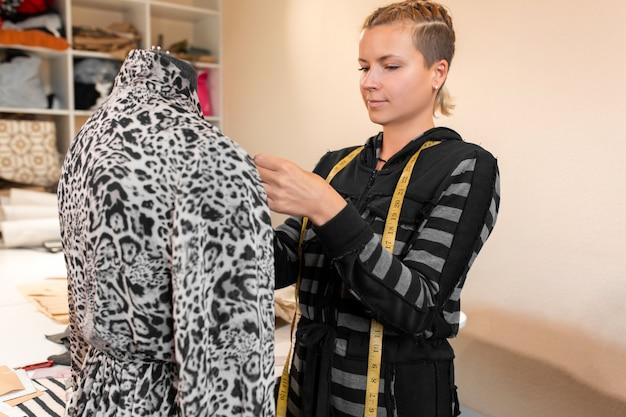 Costureira feminina, ajustando as roupas na alfaiataria manequim e sorrindo