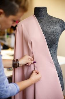 Costureira feminina anexar tecido ao manequim com agulhas