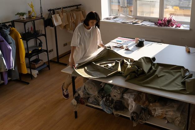 Costureira feminina costura nova coleção na oficina de tecido da moda na mesa de trabalho do ateliê