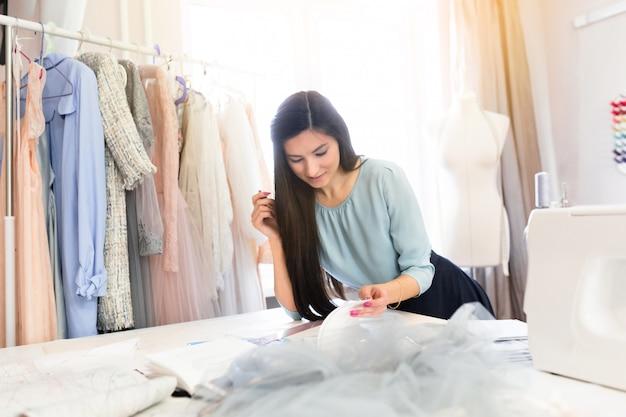 Costureira indiana alegre sentada perto de ferramentas de costura, desenha o design de roupas com um padrão em sua própria oficina