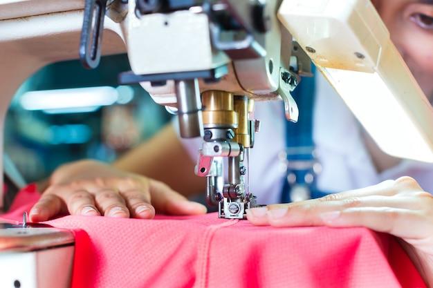 Costureira indonésia em fábrica têxtil asiática
