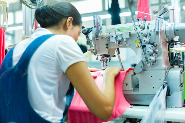 Costureira indonésia na fábrica têxtil asiática