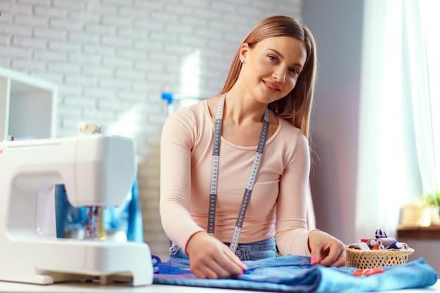 Costureira jovem alegre, sentado à mesa de trabalho em seu escritório