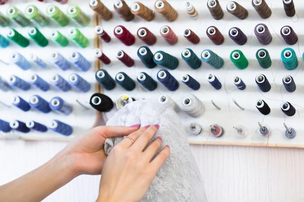 Costureira jovem seleciona tópicos para fazer uma roupa bonita e elegante.
