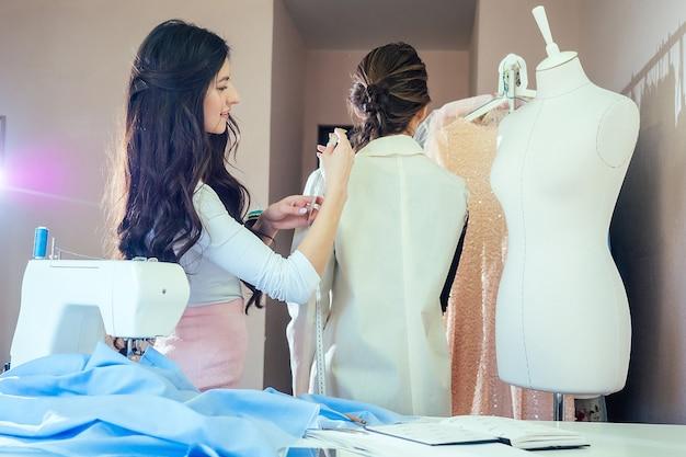 Costureira mede o cliente com uma fita métrica. alfaiate costura um terno para o cliente. costureira e garota cliente se comunicam
